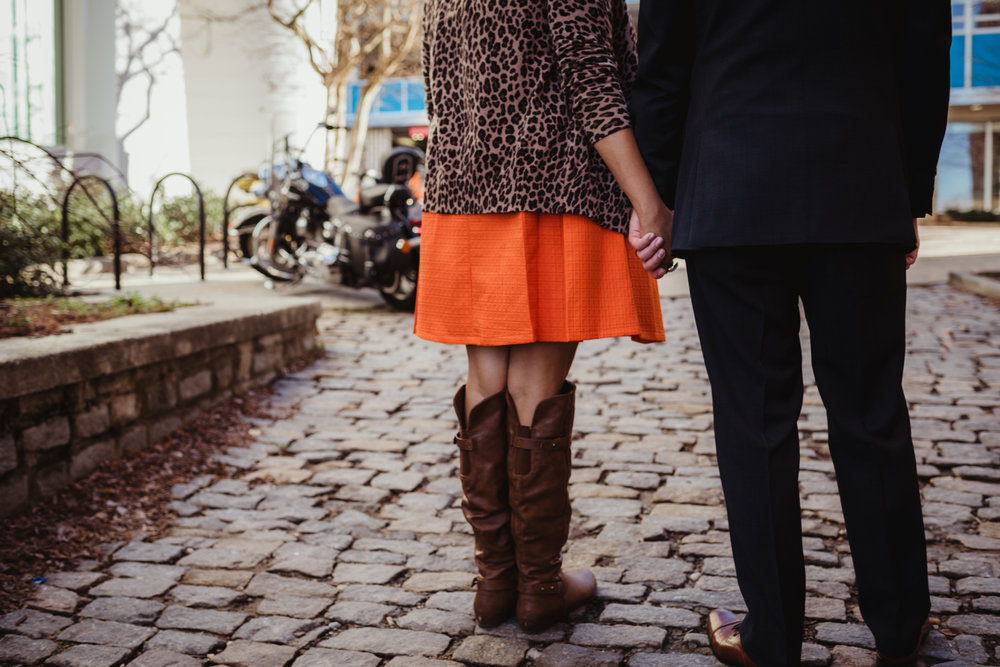 The husband and wife hold hands while walking outside of The Durham Hotel in Durham, North Carolina, image by Rose Trail Images.