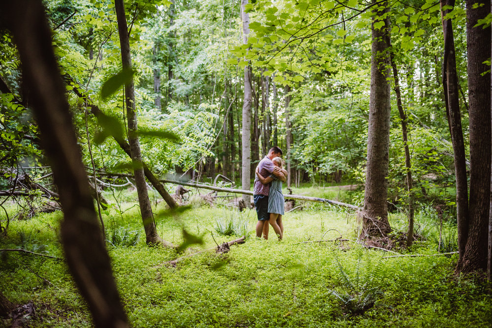 Kristin and Drew hugged in the woods during their engagement shoot in Raleigh with Rose Trail Images.