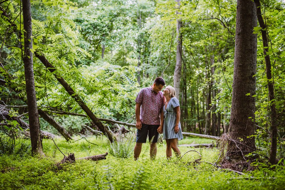 Kristin and Drew laughed in the woods during their engagement shoot in Raleigh with Rose Trail Images.