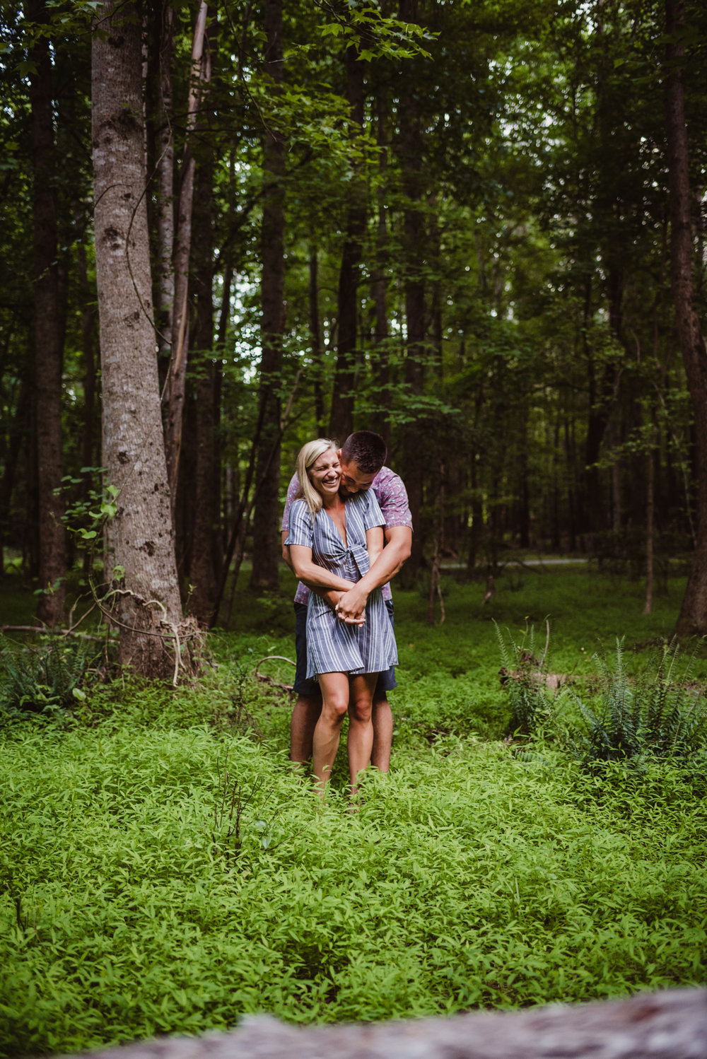 Kristin and Drew snuggled in the woods during their engagement shoot in Raleigh with Rose Trail Images.