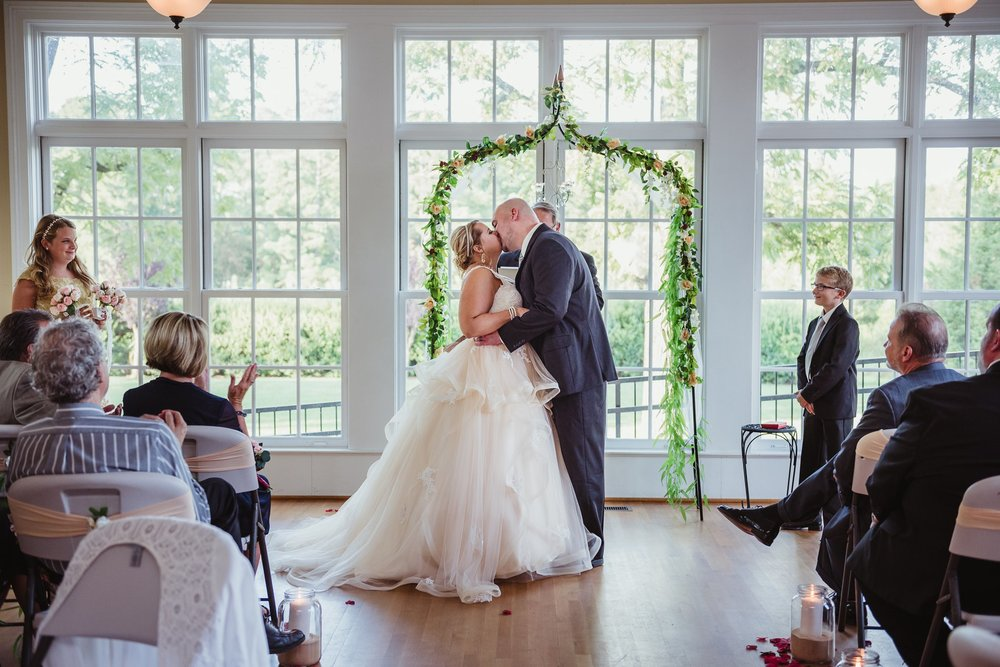 The bride and groom have their first kiss as a married couple at their wedding at the Rand-Bryan House in Raleigh, photos by Rose Trail Images.