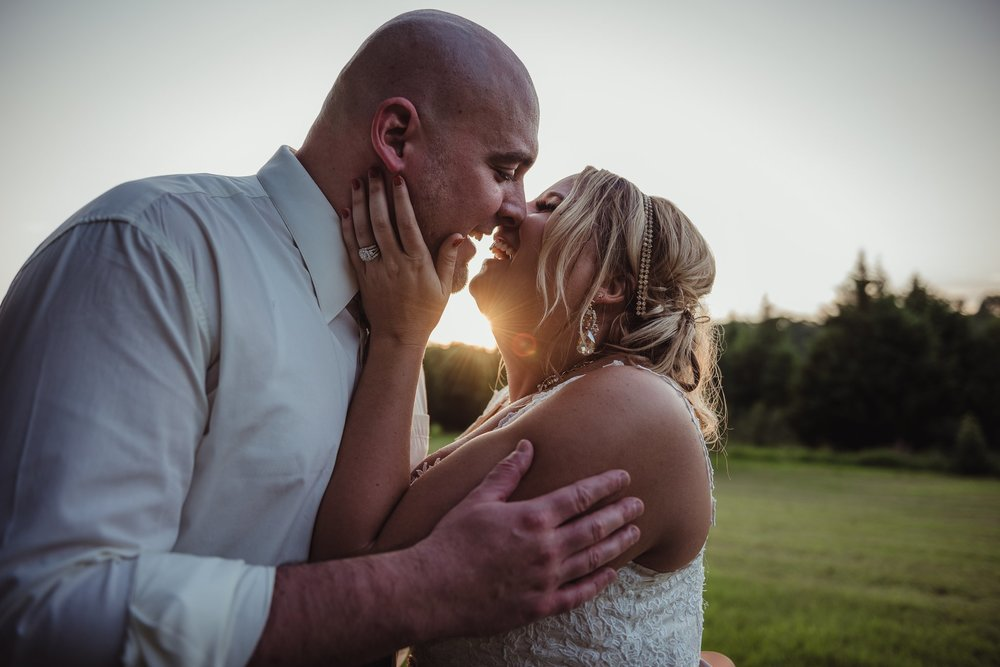 The bride and groom steal a kiss at sunset at the Rand-Bryan House in Raleigh, photo by Rose Trail Images.