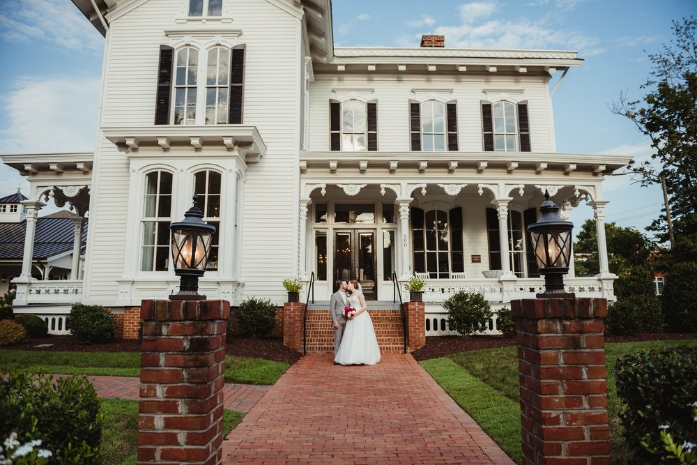 The bride and groom kiss in front of the Merrimon Wynne house in Raleigh after their wedding ceremony, photo by Rose Trail Images.