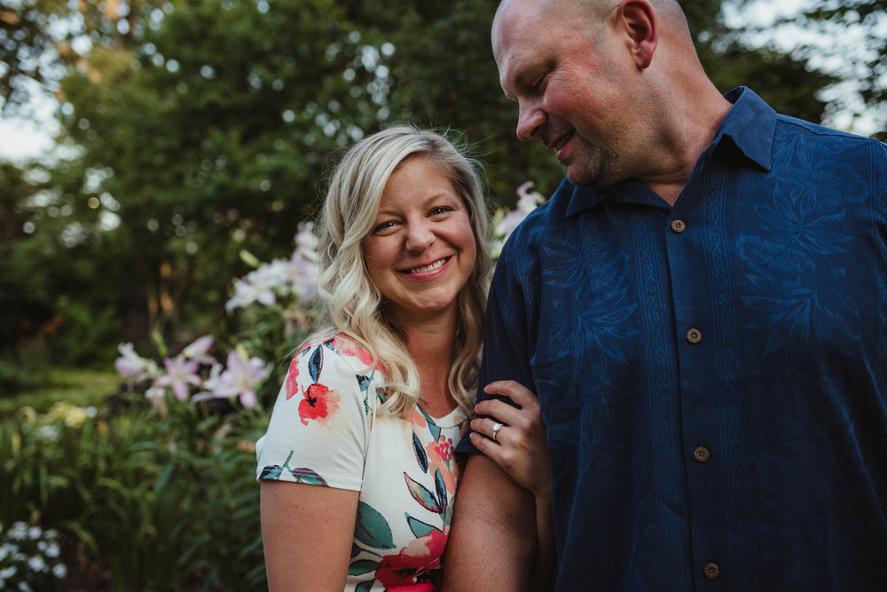 The bride-to-be smiles at Rose Trail Images while her soon to be husband looks at her while at Fred Fletcher Park in Raleigh for their engagement session.