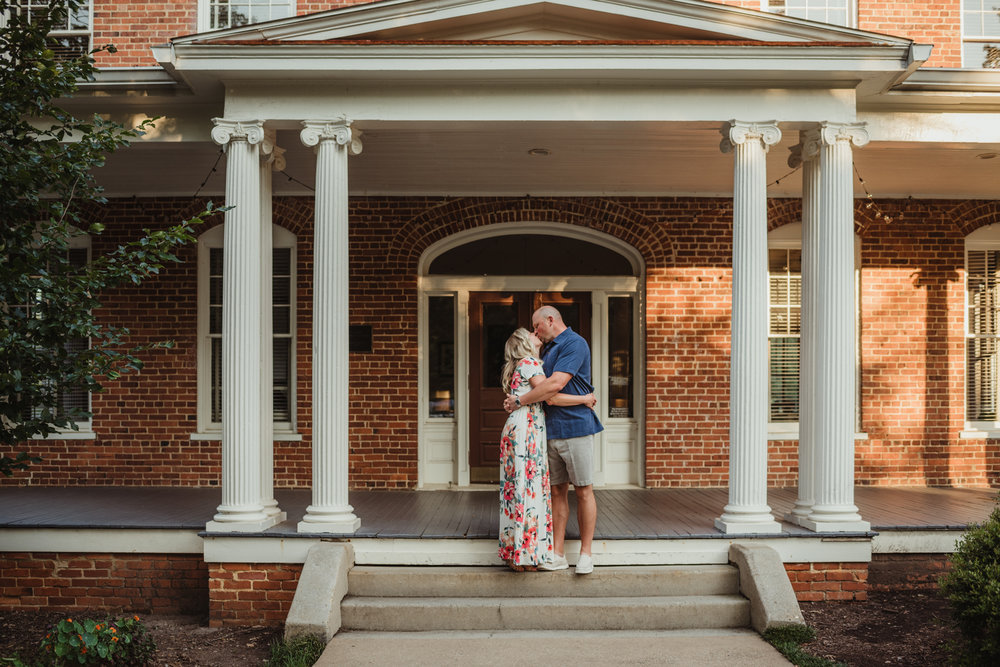 The couple kiss on the steps of the old house during their engagement session with Rose Trail Images at Fred Fletcher Park in Raleigh, North Carolina.