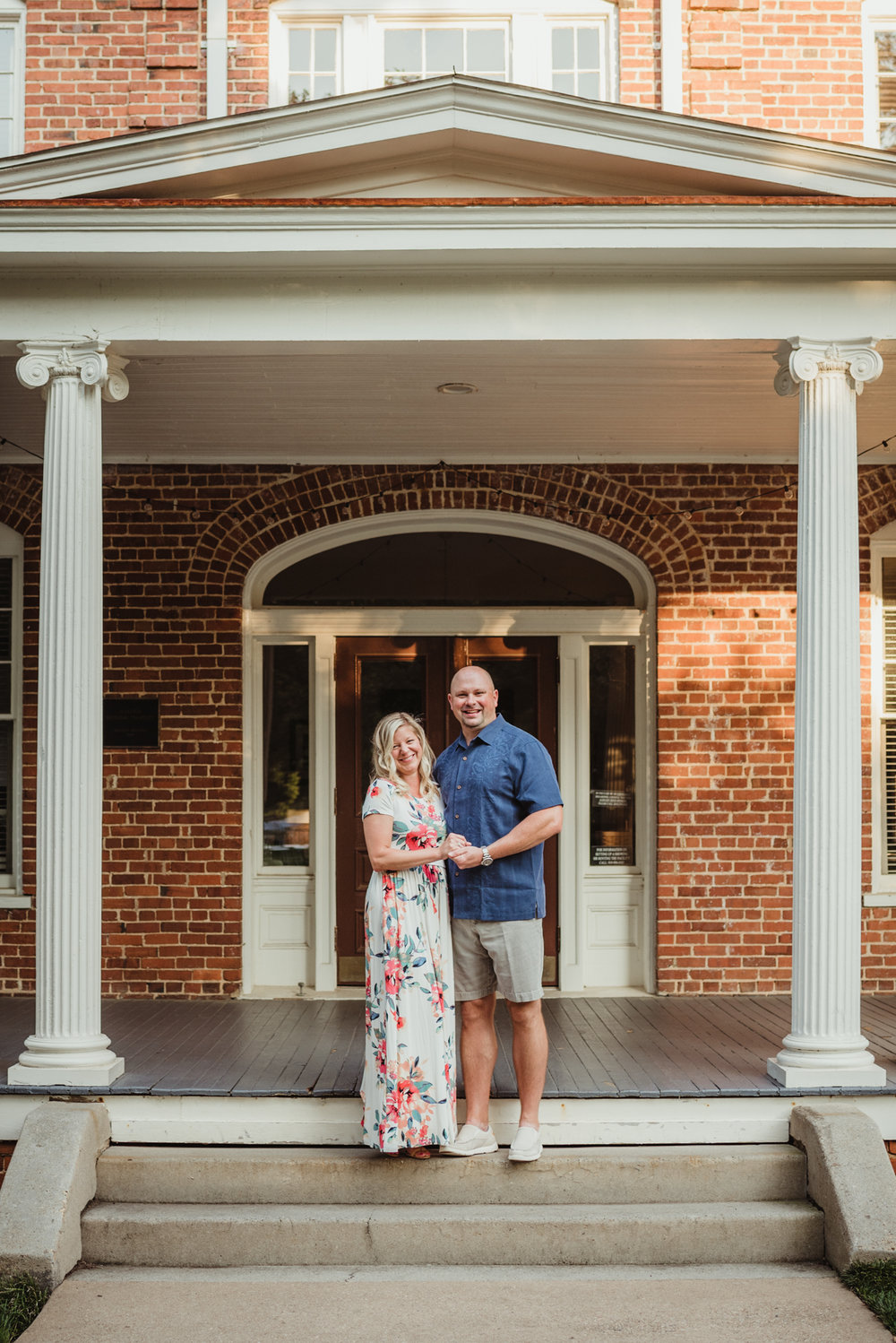 The couple stand together on the steps of the old building during their engagement session with Rose Trail Images at Fred Fletcher Park in Raleigh, North Carolina.