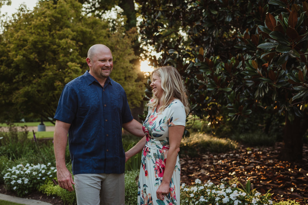 The groom tells me the story of how they met during their engagement session at Fred Fletcher Park in Raleigh, North Carolina with Rose Trail Images.