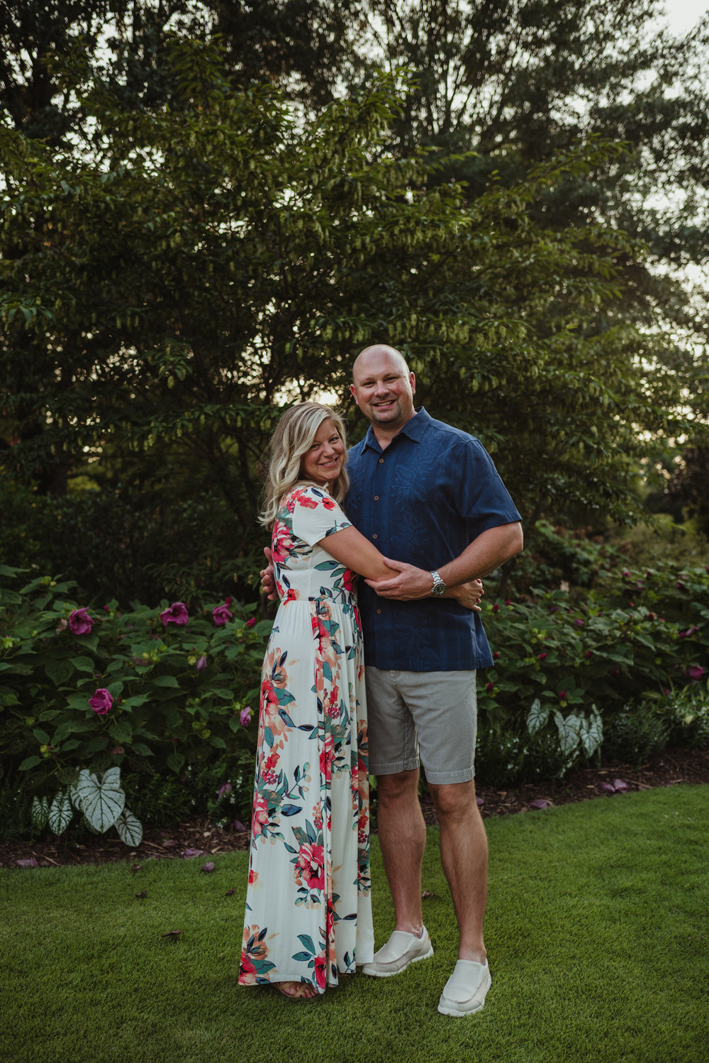 The bride and groom hold each other in the garden during their engagement session at Fred Fletcher Park in Raleigh, North Carolina with Rose Trail Images.