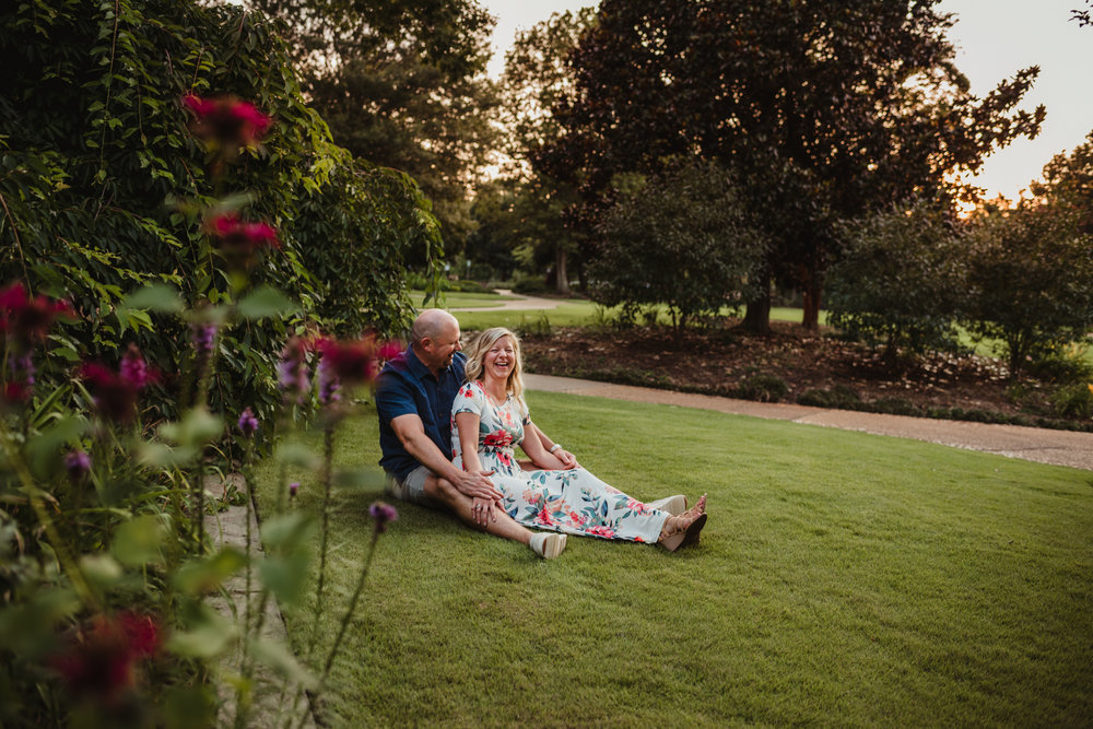 The bride and groom sit in the grass and laugh during their engagement session at Fred Fletcher Park in Raleigh, North Carolina with Rose Trail Images.
