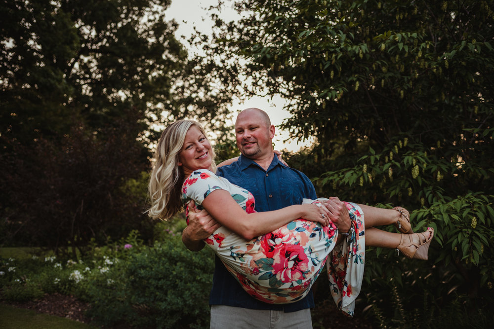 The groom picks up his bride during their engagement session at Fred Fletcher Park in Raleigh, North Carolina with Rose Trail Images.