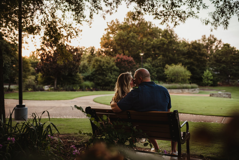 The bride and groom sneak a kiss on the bench during their engagement session at Fred Fletcher Park in Raleigh, North Carolina with Rose Trail Images.