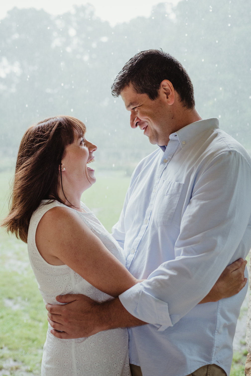 The bride and groom to be hold each other in the shelter during the rainstorm in Raleigh, during their engagement session with Rose Trail Images.