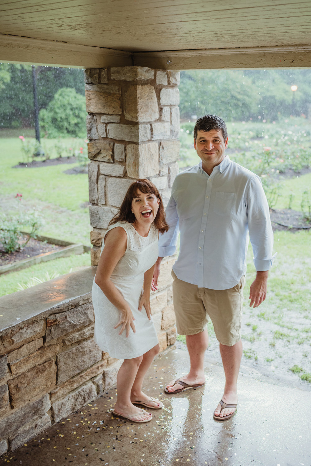 The bride and groom to be laugh at the camera during the rainstorm in Raleigh, during their engagement session with Rose Trail Images.