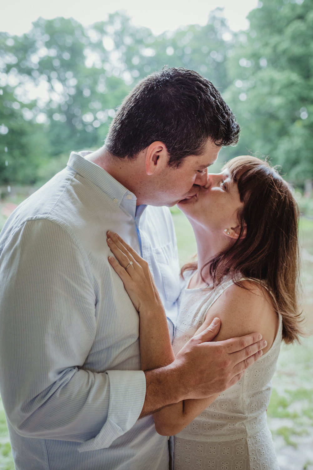 The bride and groom to be kiss each other in the shelter during the rainstorm in Raleigh, during their engagement session with Rose Trail Images.