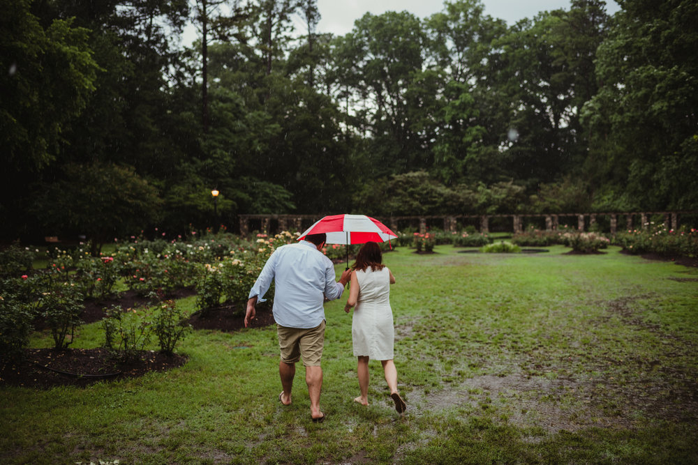 The bride and groom to be hold go under the umbrella during the rainstorm in Raleigh, during their engagement session with Rose Trail Images.