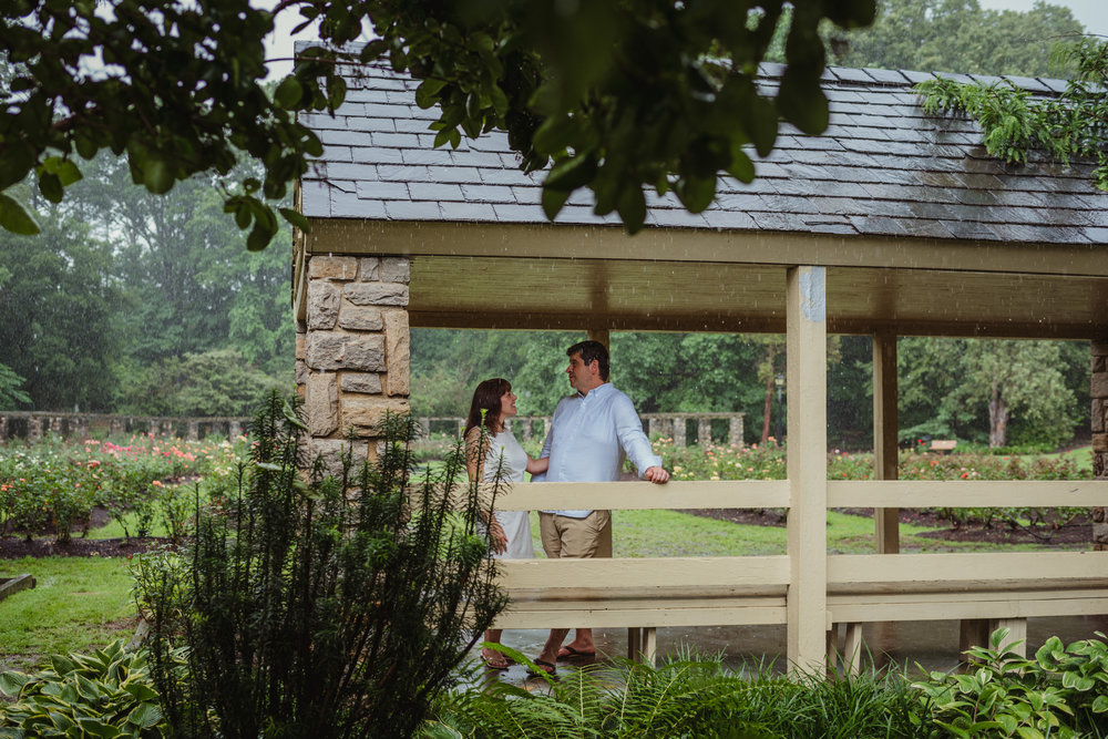 The bride and groom to be stand under the shelter during the rainstorm in Raleigh, during their engagement session with Rose Trail Images.