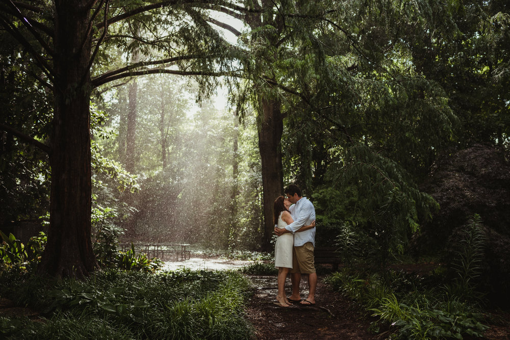 The bride and groom to be kiss in the rain and sunray during the rainstorm in Raleigh, during their engagement session with Rose Trail Images.