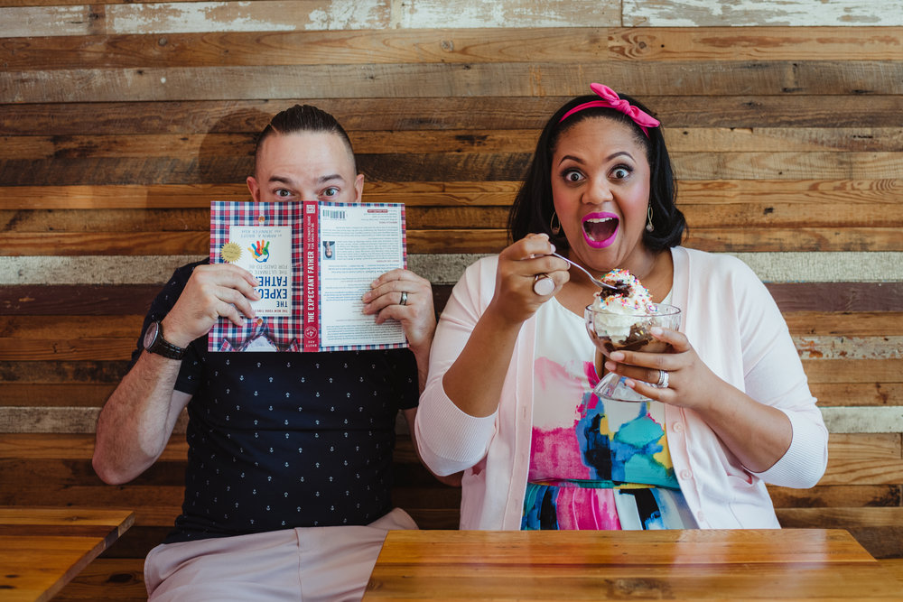 The parents to be eat a sundae and read a parenting book at The Parlour in Durham during their baby announcement photo session with Rose Trail Images.
