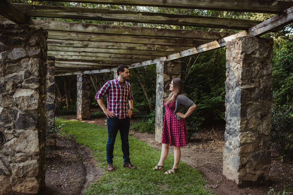 The bride and groom to be pose like superheros at the Raleigh Rose Garden during their engagement session with Rose Trail Images.