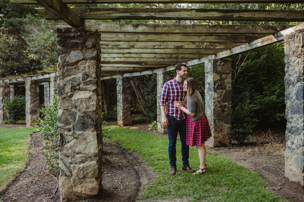 The bride and groom to be hold each other under the stone trellis at the Raleigh Rose Garden during their engagement session with Rose Trail Images.