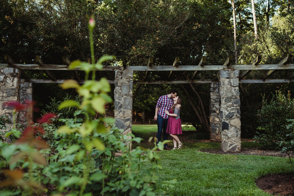 The bride and groom to be hold each other and kiss under the stone trellis at the Raleigh Rose Garden during their engagement session with Rose Trail Images.