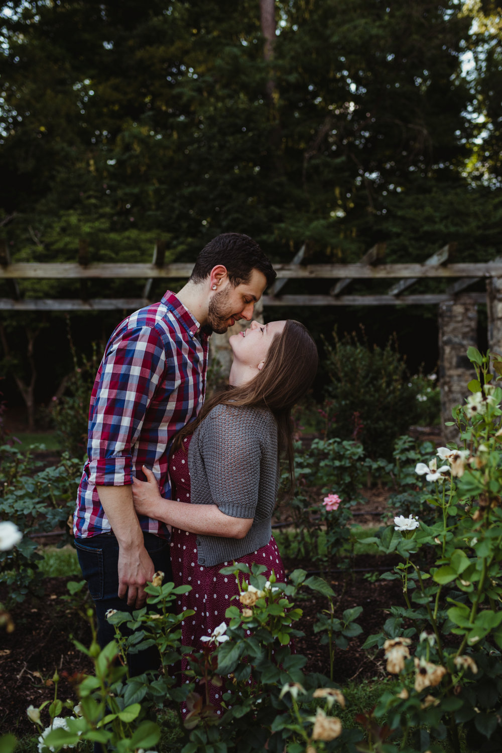 The bride and groom to be look at each other while at the Raleigh Rose Garden during their engagement session with Rose Trail Images.