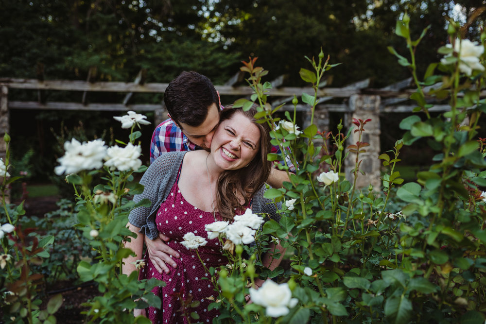 The groom kisses his bride to be on the neck while at the Raleigh Rose Garden during their engagement session with Rose Trail Images.