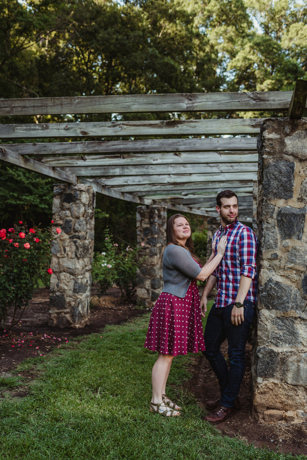 The bride and groom to be pretend to be serious under the trellis while at the Raleigh Rose Garden during their engagement session with Rose Trail Images.