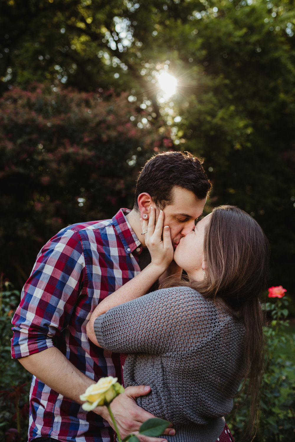 The bride and groom to be kiss under the sunset at the Raleigh Rose Garden during their engagement session with Rose Trail Images.