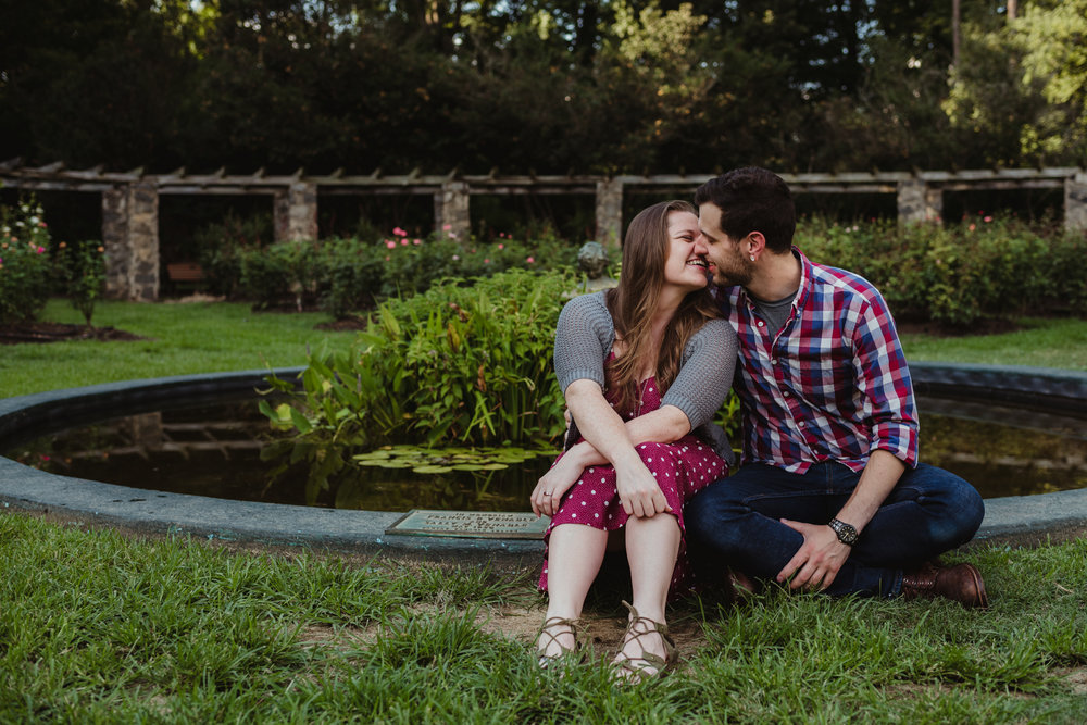 The bride and groom to be almost kiss by the pond at the Raleigh Rose Garden during their engagement session with Rose Trail Images.