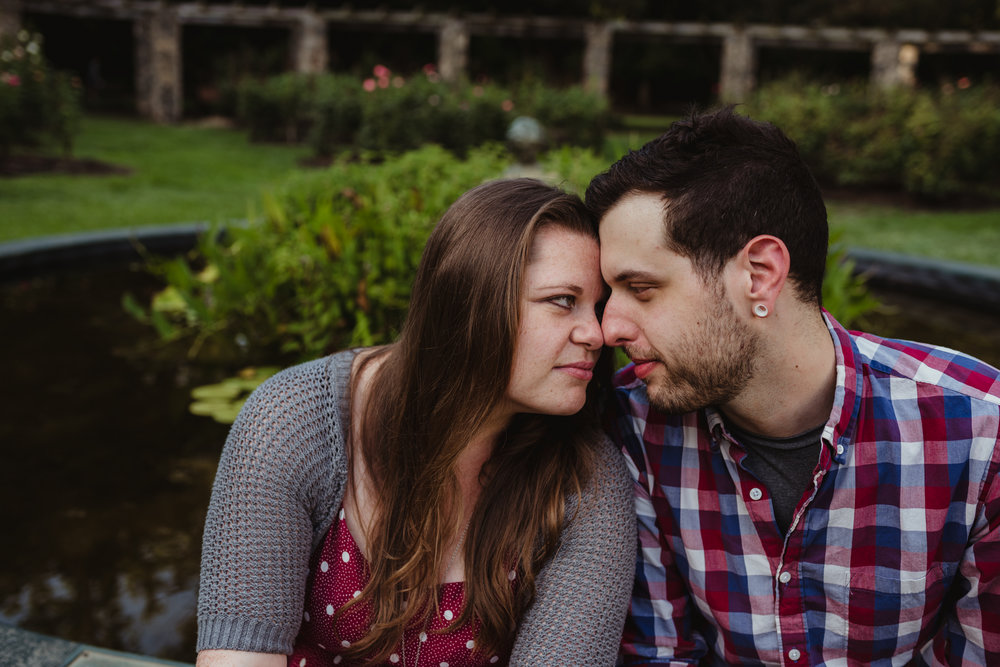 The bride and groom to be touch foreheads by the pond at the Raleigh Rose Garden during their engagement session with Rose Trail Images.