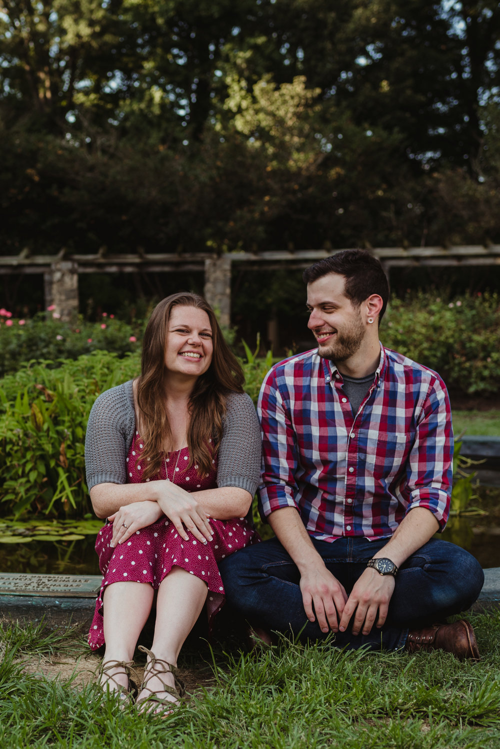 The groom to be stares at his fiancee by the pond at the Raleigh Rose Garden during their engagement session with Rose Trail Images.