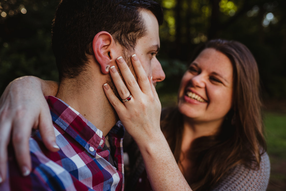 The bride to be holds her fiance's face and shows off her ruby engagement ring at the Raleigh Rose Garden during their engagement session with Rose Trail Images.