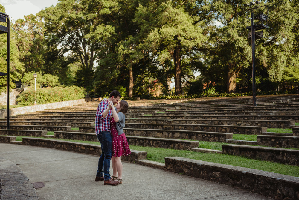 The bride and groom to be practice their first dance the Little Theater at the Raleigh Rose Garden during their engagement session with Rose Trail Images.