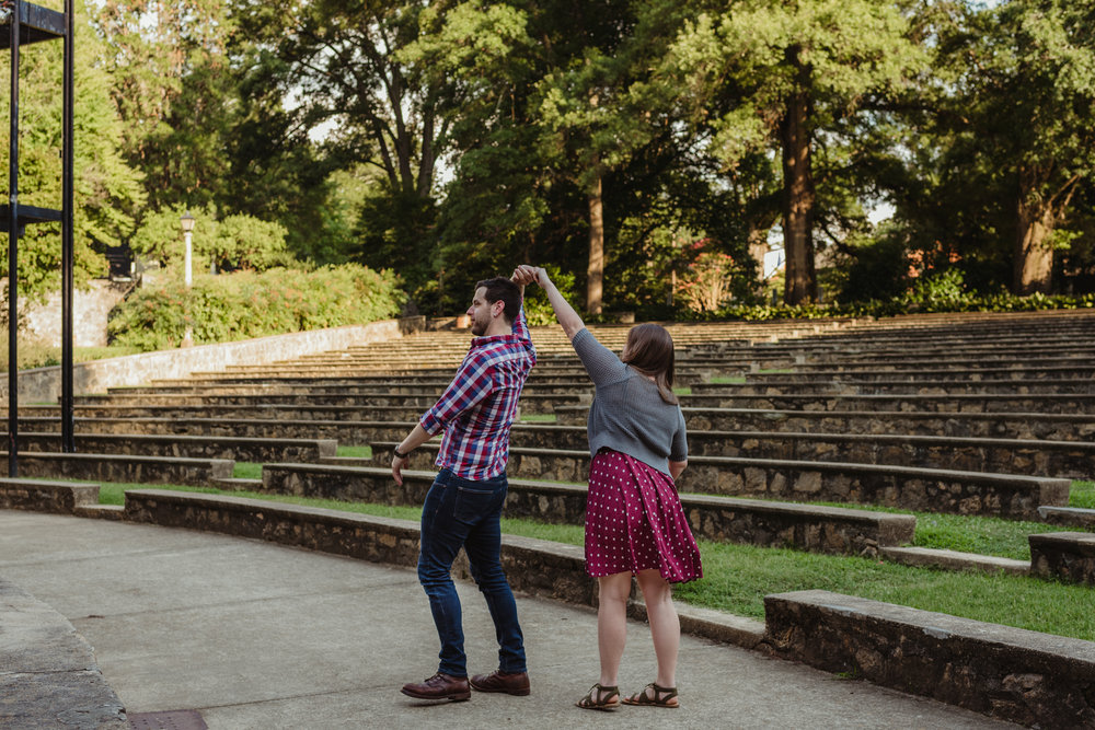 The bride and groom to be practice their first dance by twirling each other at the Little Theater at the Raleigh Rose Garden during their engagement session with Rose Trail Images.