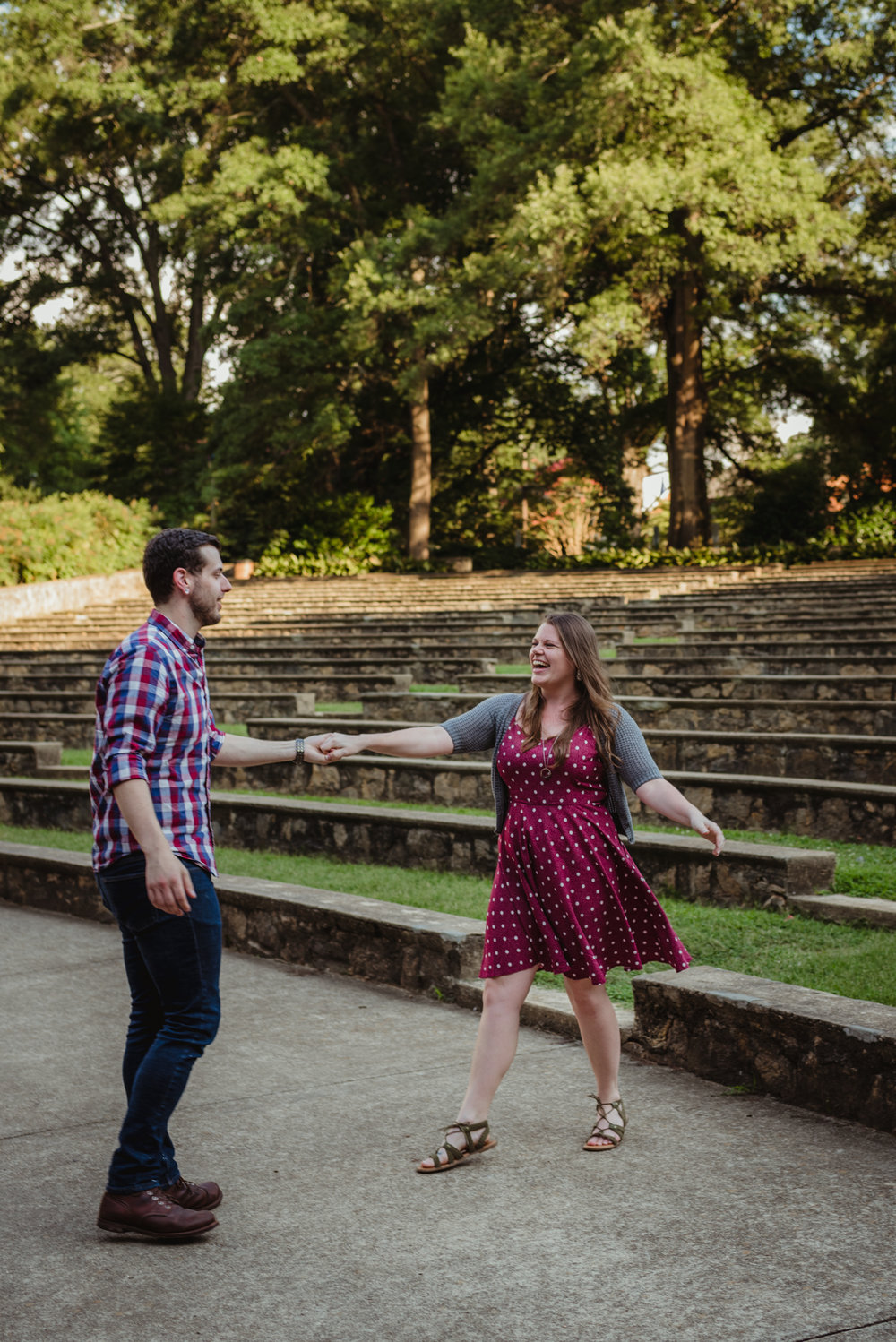The bride and groom to be practice their first dance by twirling and laughing at the Little Theater at the Raleigh Rose Garden during their engagement session with Rose Trail Images.