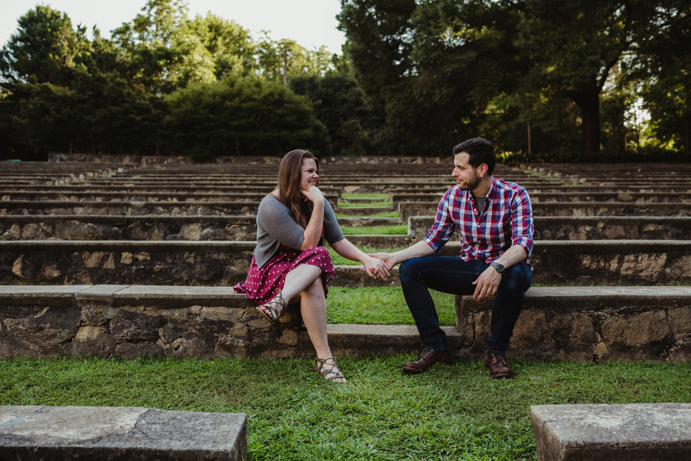 The bride and groom to be sit and hold hands at the Little Theater at the Raleigh Rose Garden during their engagement session with Rose Trail Images.
