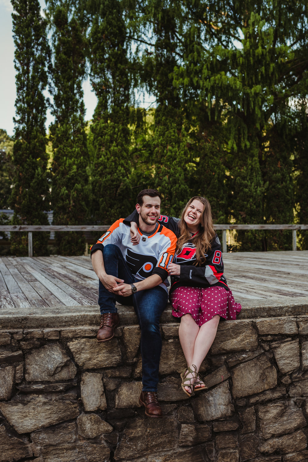 The bride and groom to be, in their Flyers and Hurricanes hockey jerseys, laugh together on the Little Theater stage at the Raleigh Rose Garden during their engagement session with Rose Trail Images.