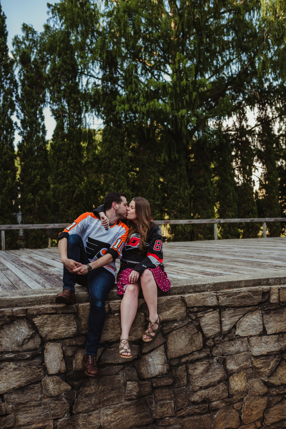 The bride and groom to be, in their Flyers and Hurricanes hockey jerseys, kiss on the Little Theater stage at the Raleigh Rose Garden during their engagement session with Rose Trail Images.