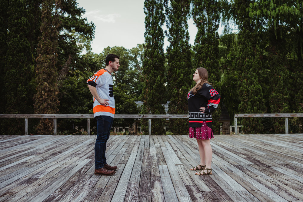 The bride and groom to be, in their Flyers and Hurricanes hockey jerseys, stand and make faces at each other on the Little Theater stage at the Raleigh Rose Garden during their engagement session with Rose Trail Images.