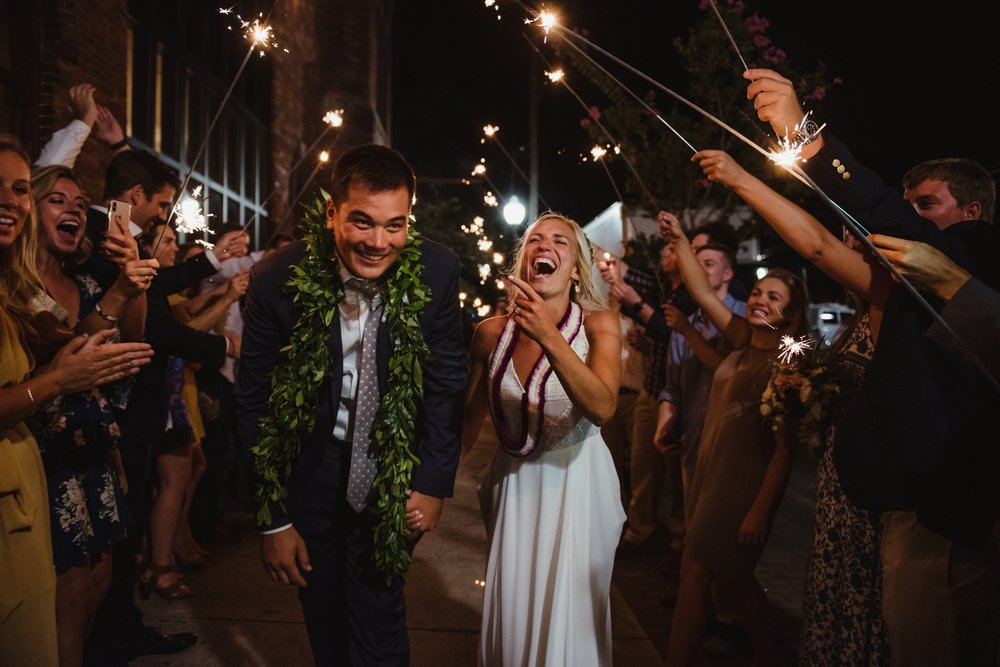 The bride and groom run through their sparkler exit after their wedding reception in Wilmington, NC, photo by Rose Trail Images.
