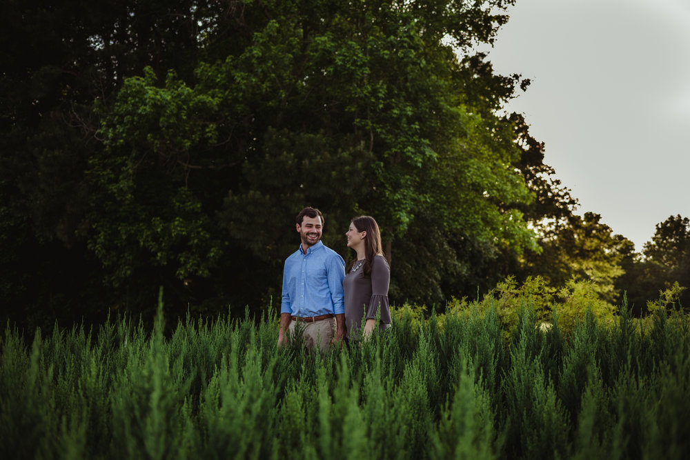 The bride and groom to be stand in with the baby Christmas trees during their engagement pictures with Rose Trail Images at their family farm in Benson, North Carolina.