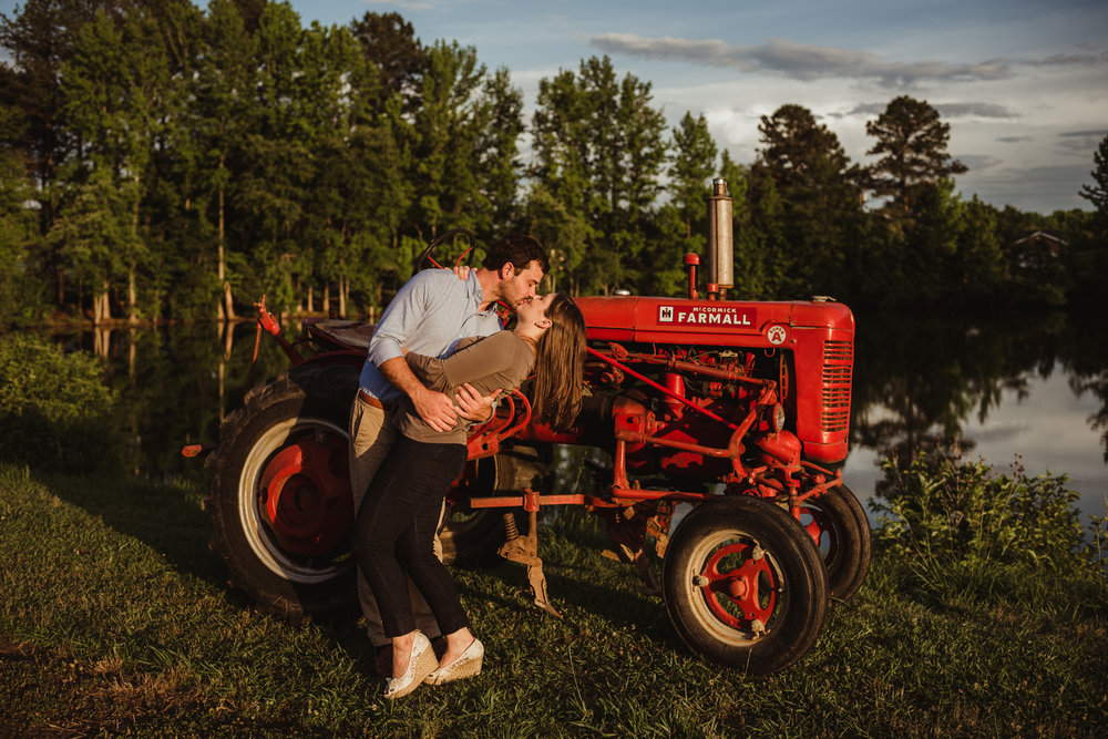 The bride and groom to be kiss in front of his grandfather's tractor for their engagement pictures with Rose Trail Images at their family farm in Benson, North Carolina.