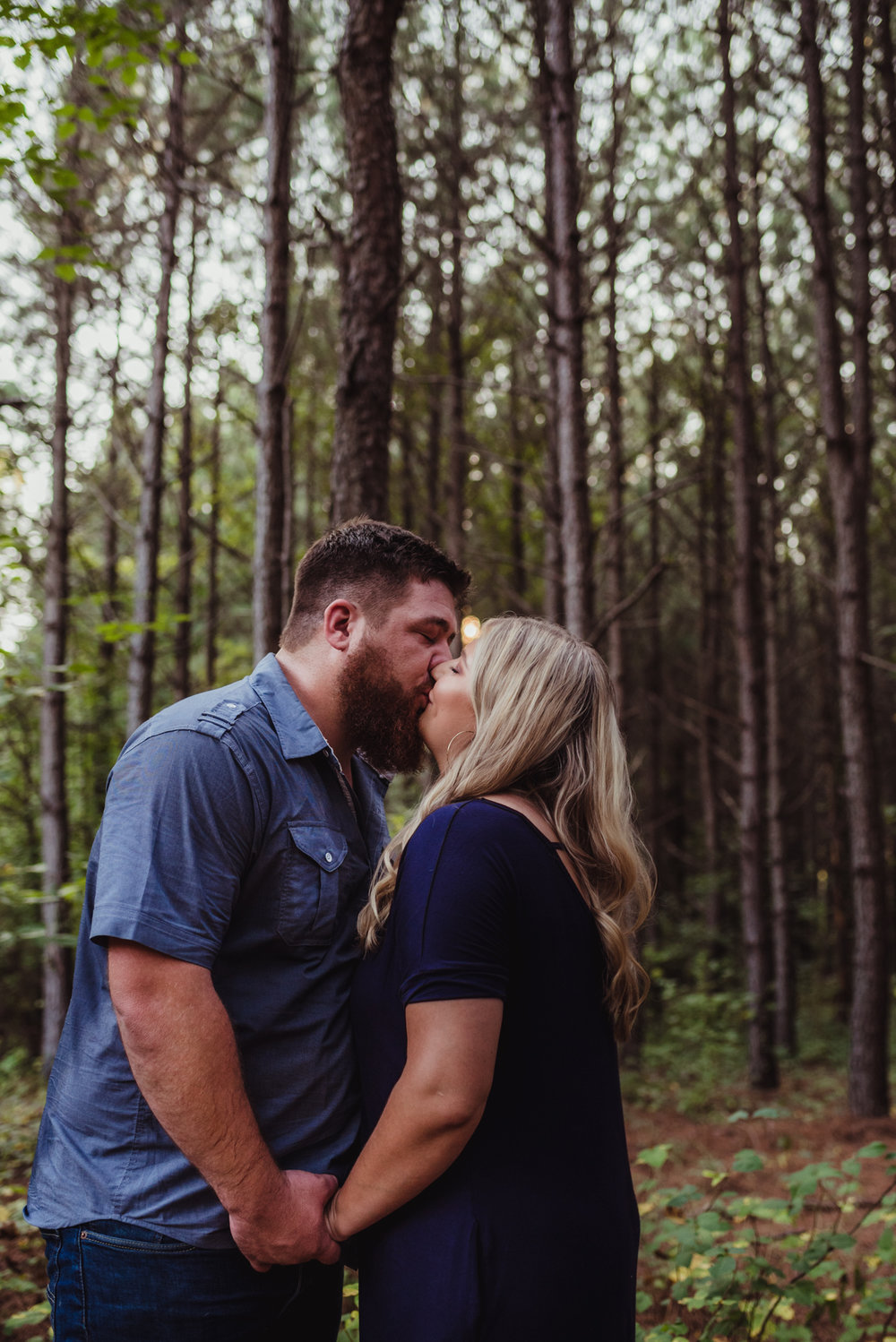The future bride and groom sneak a kiss in the woods for their engagement pictures with Rose Trail Images.