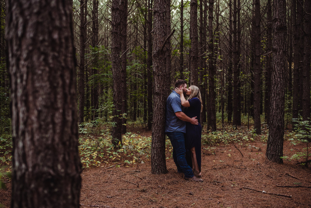 The future bride and groom kiss in the woods at the Warren Estate for their engagement pictures with Rose Trail Images.