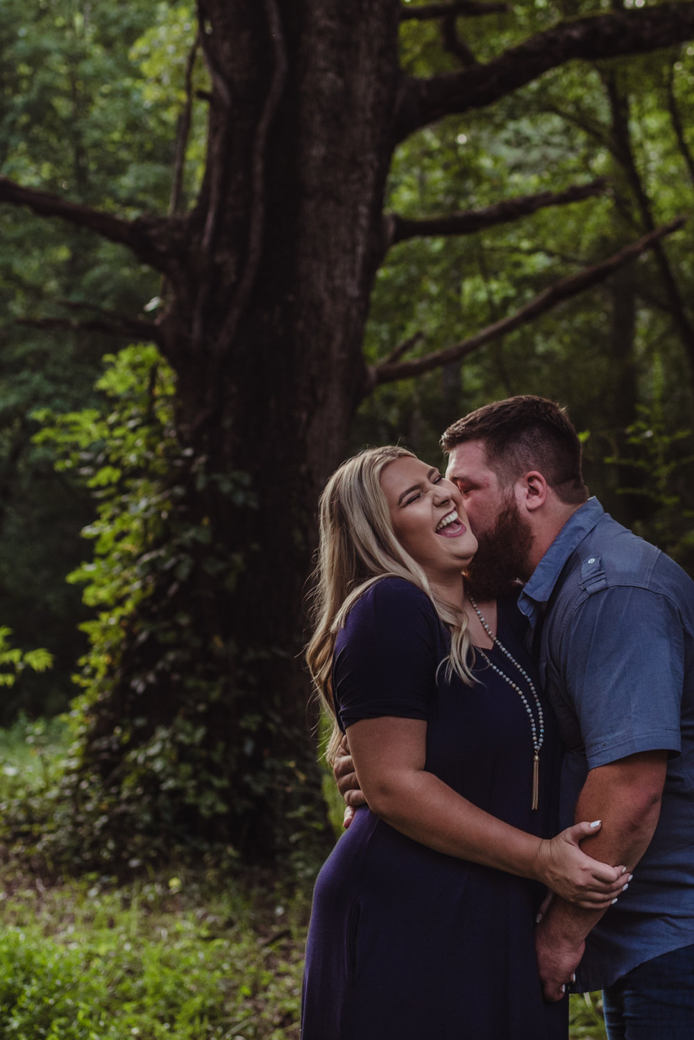 The future bride and groom laugh together in the woods for their engagement pictures with Rose Trail Images.