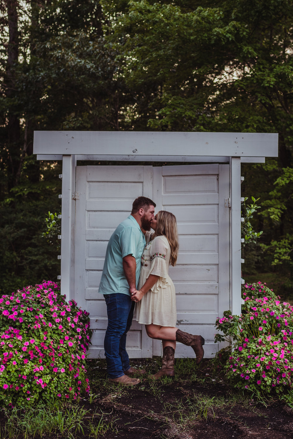 The future bride and groom kiss at the doors by the barn at the Warren Estate during sunset for their engagement pictures with Rose Trail Images.