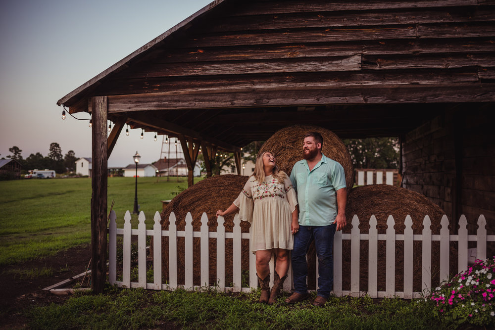 The future bride and groom hang out  by the hay bales during sunset for their engagement pictures at The Warren Estate with Rose Trail Images.