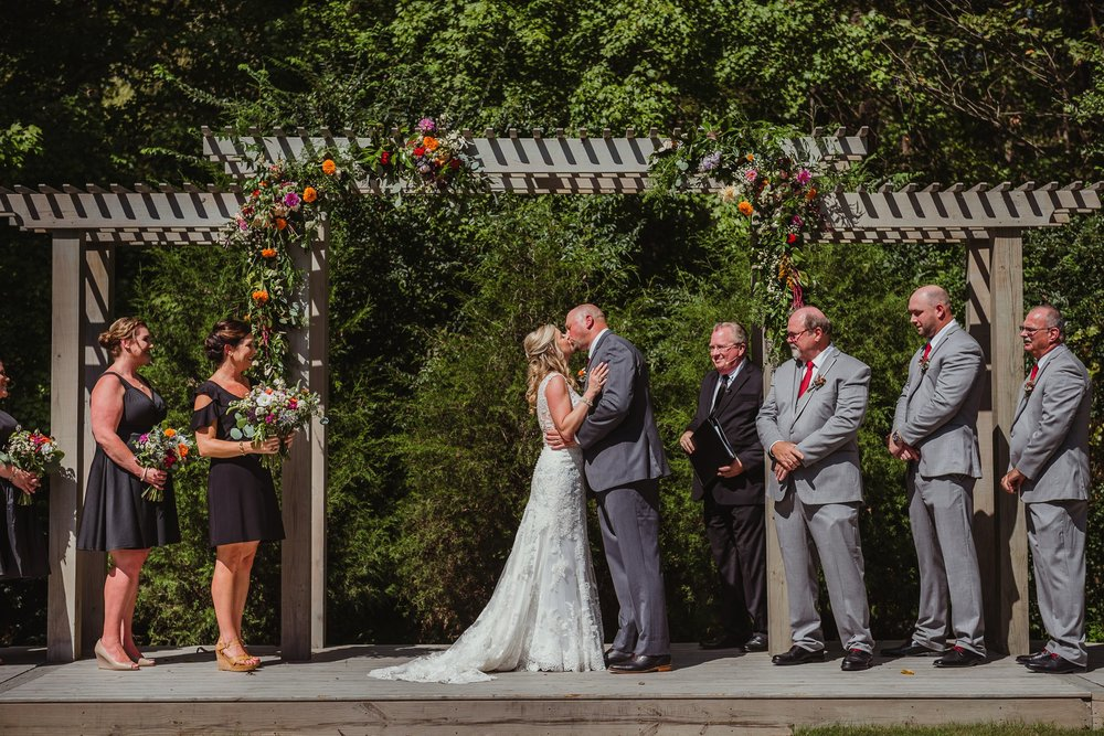 The bride and groom share their first kiss during their wedding ceremony at Cedar Grove Acres near North Carolina, picture from Rose Trail Images.