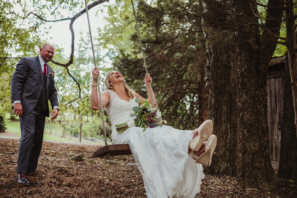 The bride and groom have fun on the swing after their wedding ceremony at Cedar Grove Acres near North Carolina, picture by Rose Trail Images.